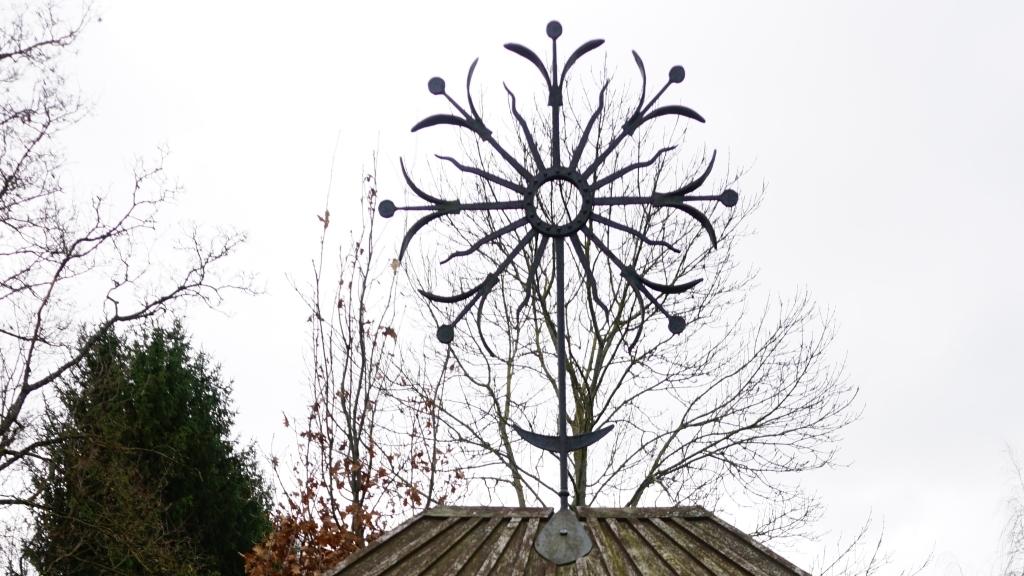 Kryželis-saulutė virš atminimo lentos Kartenoje kovotojams už laisvę