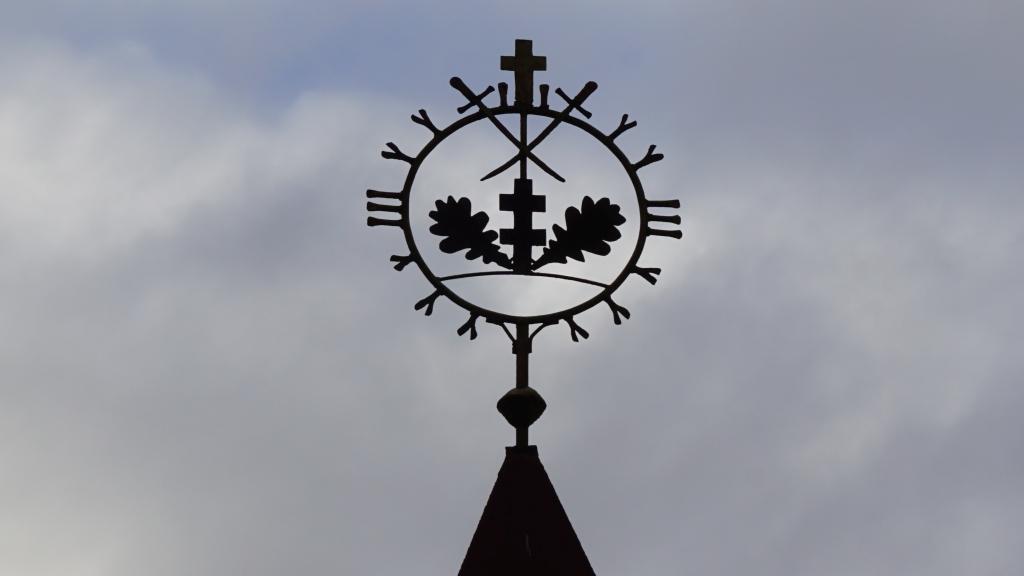 Kaltinė ornamentuota ažūrinė saulutė virš Memorialinės koplyčios Kartenos kapinėse
